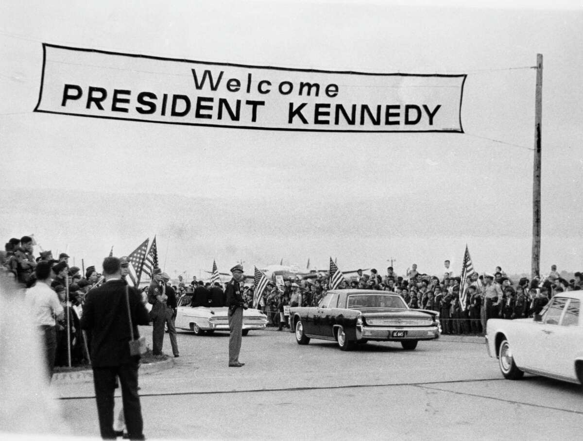 """President John F Kennedy and his motorcade are greeted with """"Welcome President Kennedy"""" sign as he arrives in Houston on Sept. 12, 1962."""