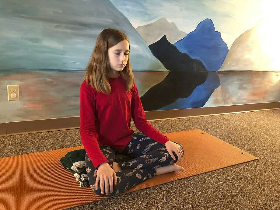 In this May 14, 2019 photo, Aeva Schifferli, 12, demonstrates a stress-relieving breathing exercise at her mother's yoga studio in East Aurora, N.Y. Her mother Erin Schifferli plans to wait until Aeva is 16 before getting her a cellphone out of concern that the technology, especially social media, is contributing to rising levels of anxiety and depression among teenagers. (AP Photo/Carolyn Thompson) Photo: Carolyn Thompson, Associated Press