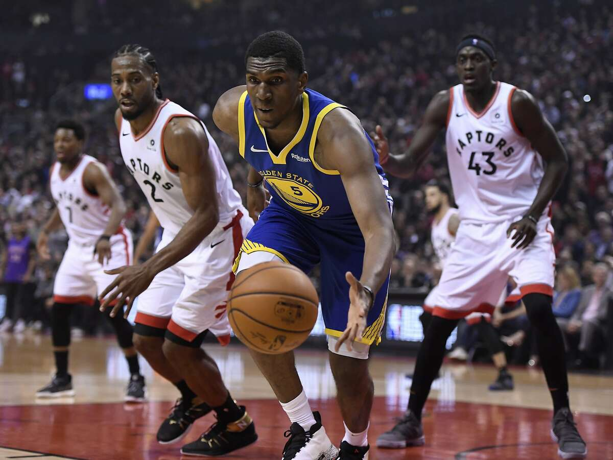 Golden State Warriors center Kevon Looney (5) tracks down a loose ball while watched by Toronto Raptors' Kawhi Leonard (2) and Pascal Siakam (43) during the first half of Game 1 of basketball's NBA Finals, Thursday, May 30, 2019, in Toronto. (Frank Gunn/The Canadian Press via AP)