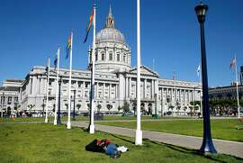 A man sleeps in Civic Center Plaza in front of City Hall in San Francisco, Calif. on Friday, June 7, 2019.