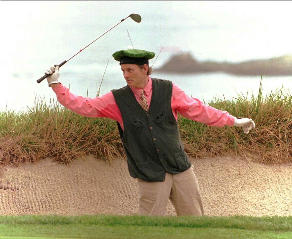 Actor Bill Murray, wearing a green tam-o-shanter with a flag and ball on it, dances in the sand before addressing his ball on No. 4 at Pebble Beach during the 1995 AT&T Pro-Am.