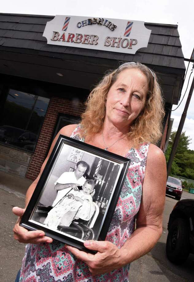 Sixth-generation barber Maria Mazzacane Perez holds an old photograph of her father, Joseph Mazzacane Sr., cutting a child's hair that previously hung on the wall of the Cheshire Barber Shop. Photo: Arnold Gold / Hearst Connecticut Media / New Haven Register
