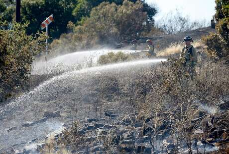 Firefighters extinguish hotspots from a four-alarm fire that consumed 24 acres on a dry hillside in Cordelia, Calif. on Friday, June 7, 2019.