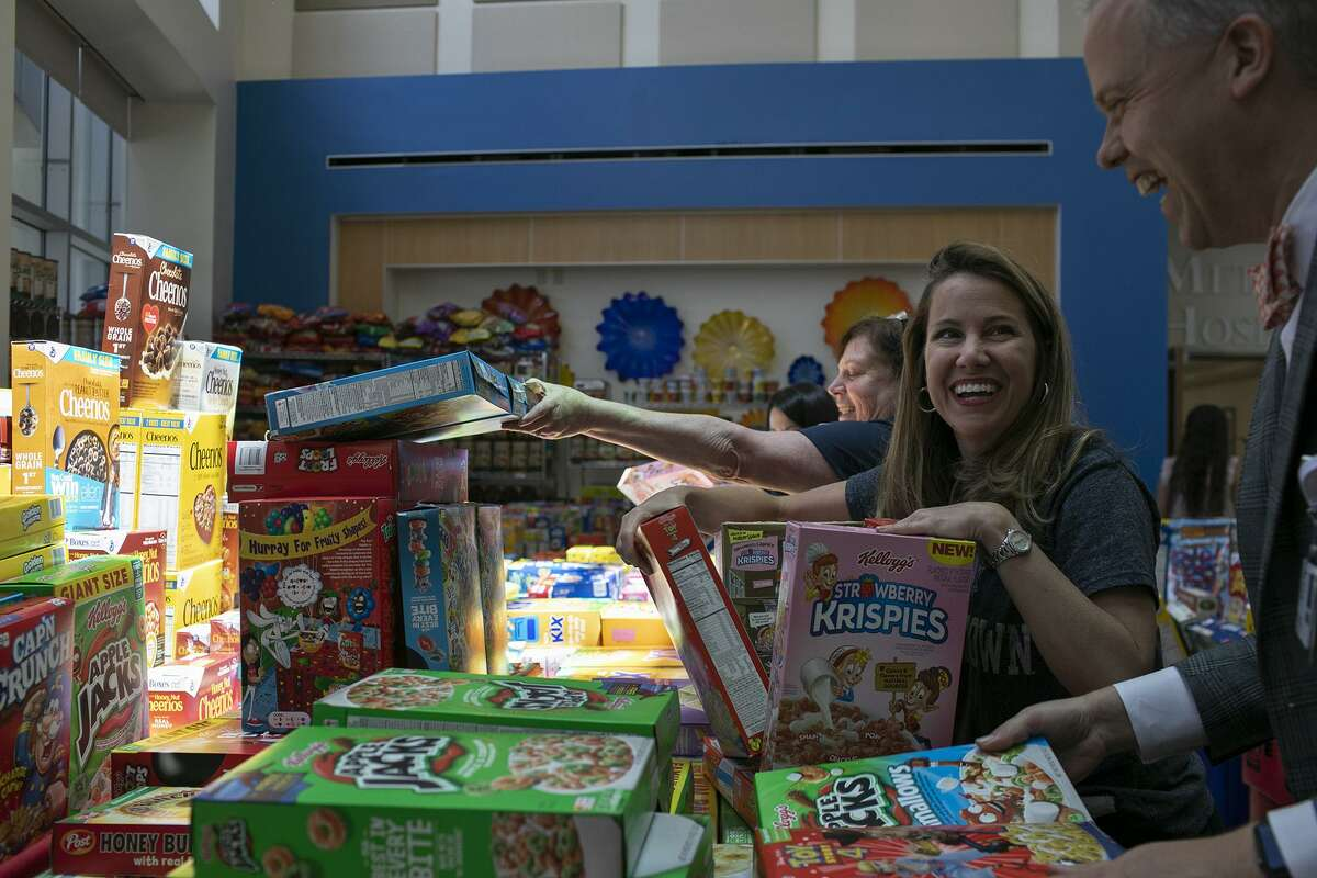 Dr. Amy Holder, one of Rowan Windham's ICU doctors, helps load cereal Friday with Methodist Children's Hospital's chief medical officer, Dr. Peter DeYoung, right, during the Rowan Windham Memorial Cereal Drive.