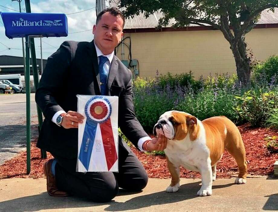 Jose Miguel Sanchez, a friend of Kara Gordon of Midland, poses with Thor the bulldog after he won 'Best in Show' at the Midland Michigan Kennel Club show on Thursday, June 6, at the Midland County Fairgrounds. (Photo provided)