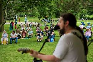 Dave Miller, lead singer of the mid-Michigan band The Etceteras, sings a cover of 'Stuck in the Middle with You' by Stealers Wheel with the rest of his band during Tunes by the Tridge in Chippewassee Park. (File photo)