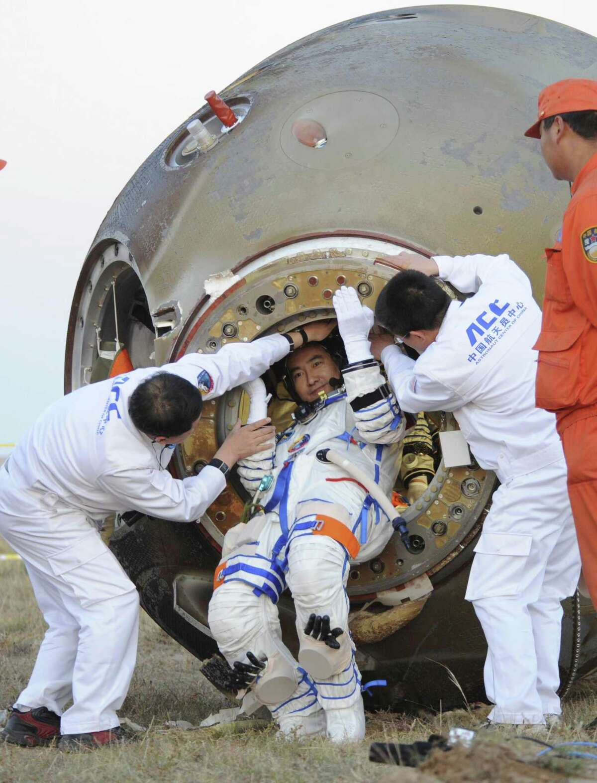 In this photo released by China's Xinhua News Agency, Chinese taikonaut Zhai Zhigang is helped to get out of the Shenzhou-7 re-entry module after its safe landing in Siziwang Banner in North China's Inner Mongolia Autonomous Region on Sept. 28, 2008. Zhai conducted the country's first-ever spacewalk in the mission.