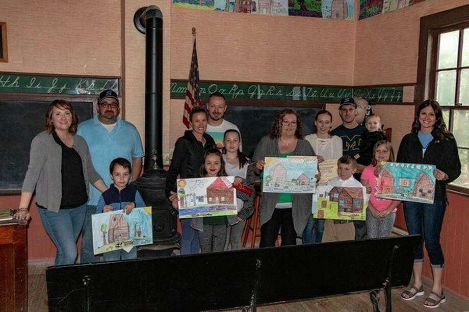 Art teacher Allison Brady standing on the right, poses with the winners of the 2019 Log Cabin Art Contest as the ribbons and certificates of appreciation were recently awarded at Felix School House at the Sanford Centennial Museum. The student winners, from left, are: Porter Rutledge in first place; Presley Cozat in second place; Stephanie Zalba, who is standing in for third place, Noah Zalba; Gabe Page who received second honorable mention; and teacher Allison Brady who is standing in for first honorable mention, Riley Black. (Photo provided/Ron Hughes)