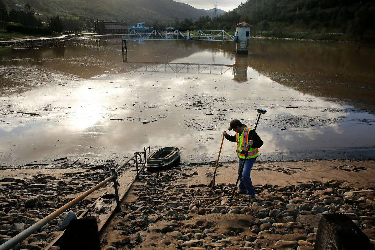 """Surveyor Tanner Neal test the integrity of the dam making sure it hasn't moved in Moccasin, Calif., as seen on Fri. March 23, 2018. Officials issued a flash flood warning Thursday for south central Tuolumne County due to """"imminent dam failure"""" at Moccasin Reservoir Dam in Tuolumne County."""