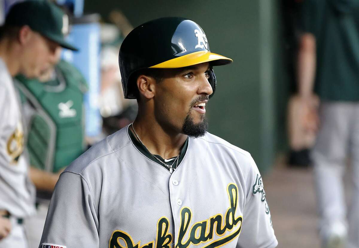 Oakland Athletics' Marcus Semien smiles as he stand in the dugout after hitting a solo home run during the fifth inning of the team's baseball game against the Texas Rangers in Arlington, Texas, Friday, June 7, 2019. (AP Photo/Tony Gutierrez)