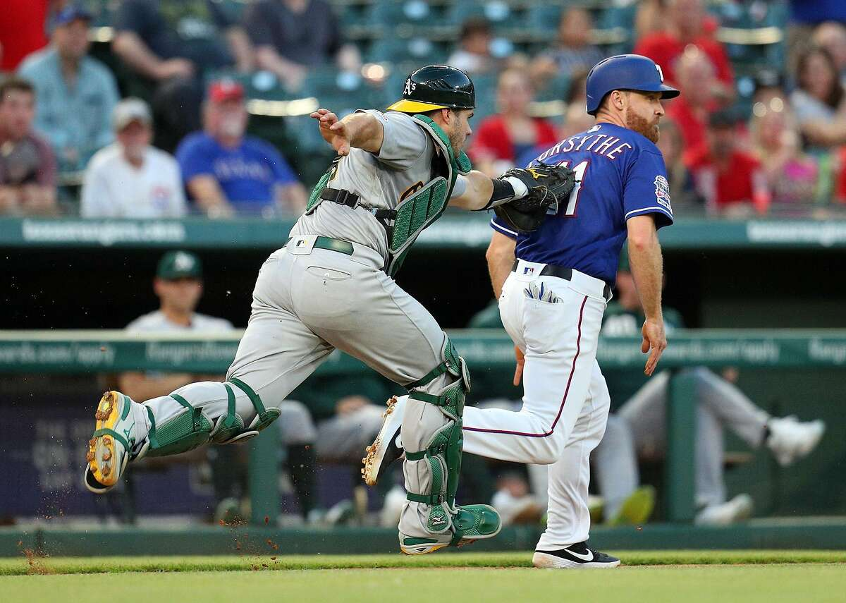 Oakland Athletics catcher Josh Phegley, left, tags out the Texas Rangers' Logan Forsythe on a rundown in the fourth inning on Friday, June 7, 2019, at Globe Life Park in Arlington, Texas. (Richard W. Rodriguez/Fort Worth Star-Telegram/TNS)