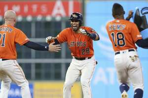 Houston Astros players Derek Fisher (21) and Tony Kemp (18) go to Robinson Chirinos (28) as his walk-off double sent Yuli Gurriel home during the bottom eleventh inning of the MLB game at Minute Maid Park on Friday, June 7, 2019, in Houston. The Houston Astros defeated the Baltimore Orioles 4-3.