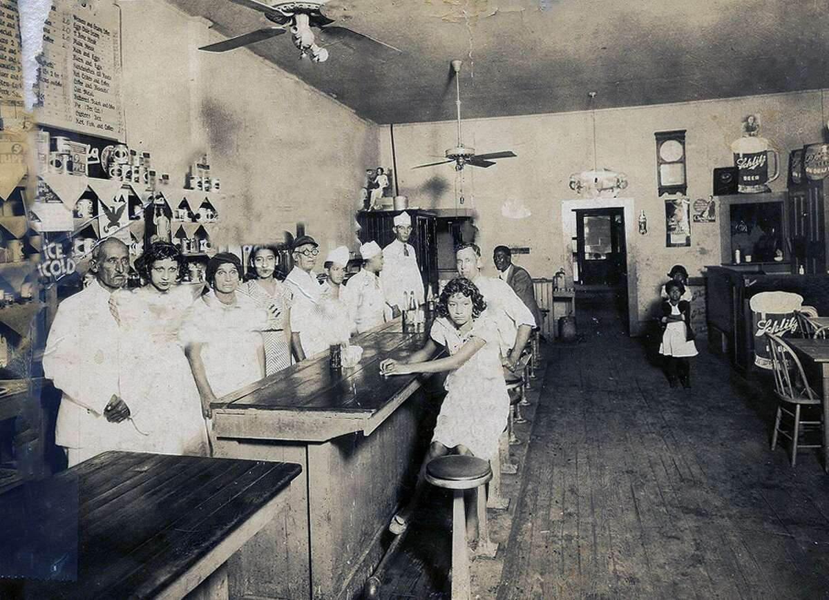 Members of the Alcoser family gather at the Brownskin Café on the East Side in this 1930s photo. Seated at the counter is Trinidad and behind her is her brother, Luis. Standing third from left behind the counter is Carolina Guzman, the family matriarch and mother of Trine and Luis. To Guzman's left is another daughter, Maggie, and to her left, wearing glasses and a dark cap, is Carolina's husband and the children's father, Francisco Alcoser Rodriguez. Many of the family members worked at the cafe.