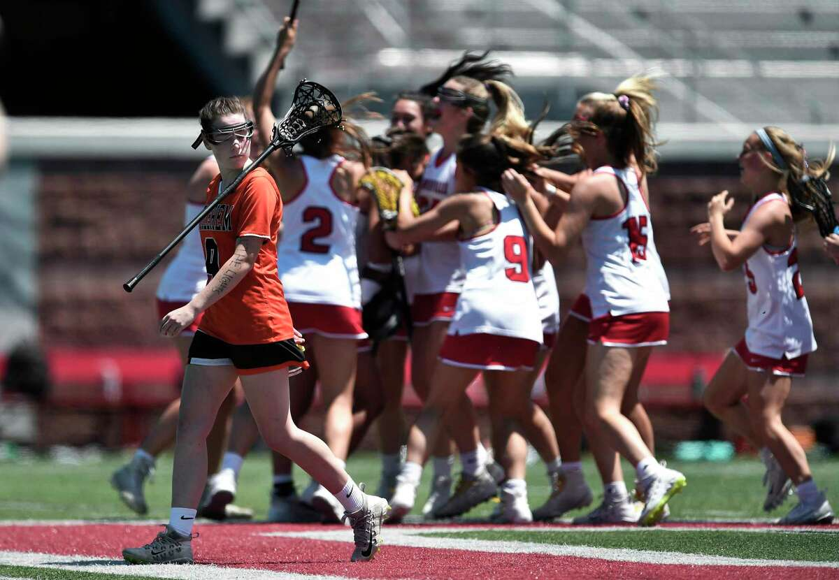 Bethlehem's Ashlynn McGrath, left, walks away as Baldwinsville players celebrate after a Class A semifinal at the NYSPHSAA Girls Lacrosse Championships in Cortland, N.Y., Friday, June 7, 2019. Bethlehem?s season ended with a 15-14 overtime loss to Baldwinsville-III. (Adrian Kraus / Special to the Times Union)