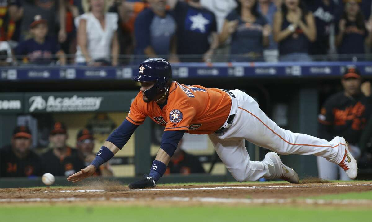 Houston Astros third baseman Yuli Gurriel (10) slides and scores the winning run with Robinson Chirinos' double as Baltimore Orioles catcher Chance Sisco (15) cannot catch the pass at home plate during the bottom eleventh inning of the MLB game at Minute Maid Park on Friday, June 7, 2019, in Houston. The Houston Astros defeated the Baltimore Orioles 4-3.