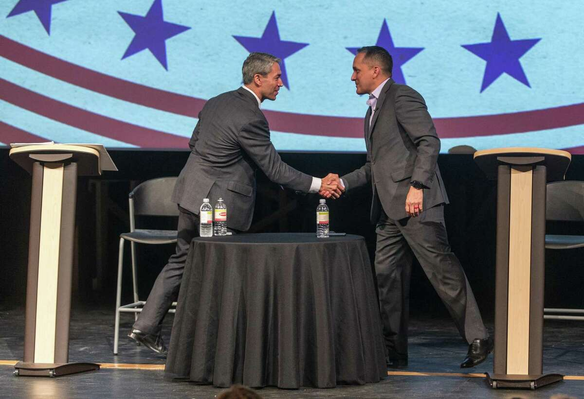 Mayor Ron Nirenberg, left, and Councilman Greg Brockhouse shake hands after participating in an AARP-sponsored forum at Palo Alto College on April 9. The two men are in a hotly contested runoff race that ends Saturday.
