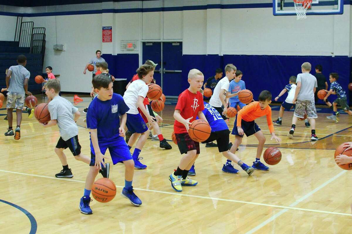Campers protect their ball while trying to knock away a competitor's ball during a skills game at the Friendswood summer basketball camp Thursday.