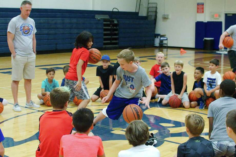 Sammy Lara (left) and Ryan Keener dribble as they try to knock each other's basketball out of the ring during a skills game at the Friendswood summer basketball camp. Observing is camp instructor David McKeel. Photo: Kirk Sides / Staff Photographer / © 2019 Kirk Sides / Houston Chronicle
