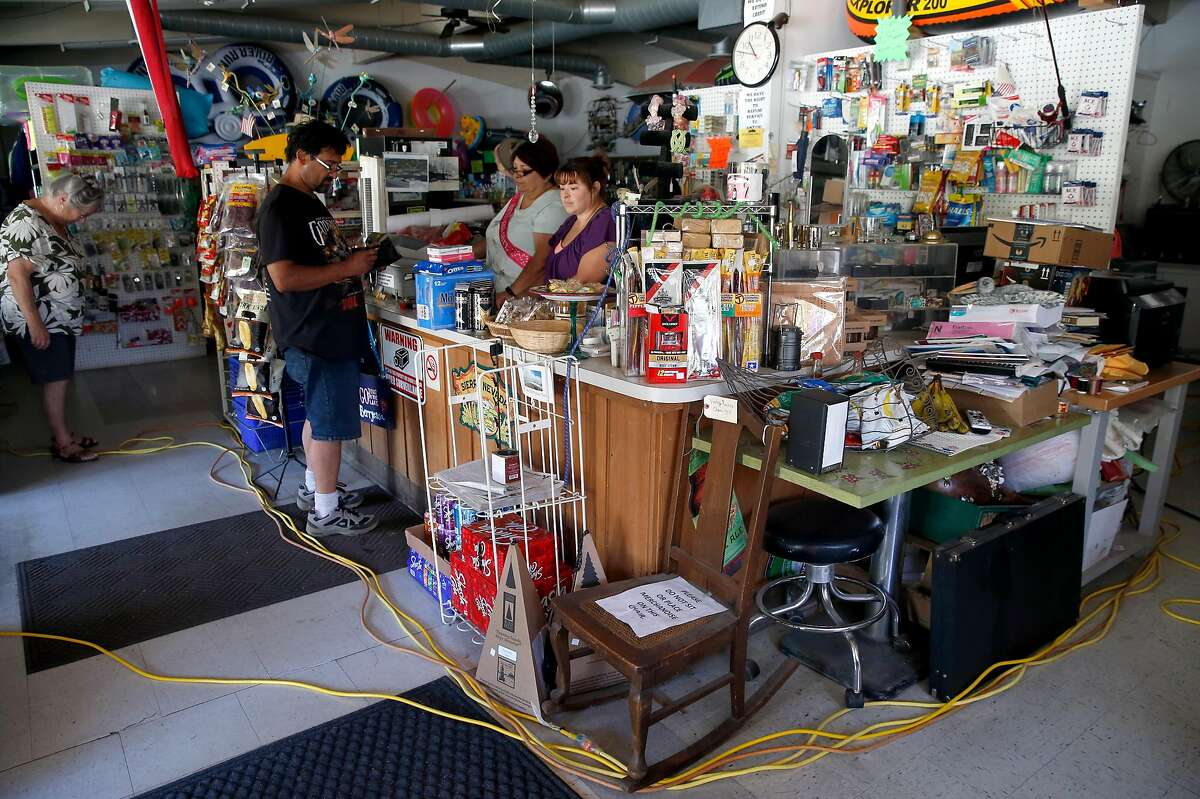 A customer purchases picnic supplies at the Spanish Flat Country Store and Deli where extension cords from a gas generator provides limited power in Lake Berryessa, Calif. on Saturday, June 8, 2019.