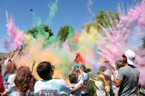 Colors fly as people run through clouds of powdered paint at the 2019 Zion Colorpalooza. The event was hosted by the Zion Lutheran Church in Harbor Beach and had inflatable fun before the color runs.