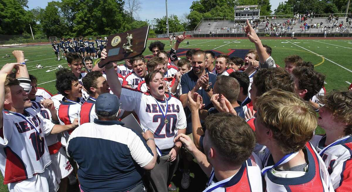 New Fairfield goalie Brennan Hart (20) hoists the championship plaque as his teammates celebrate their win over Weston in Saturday's Class M championship game at Brien McMahon High School in Norwalk.