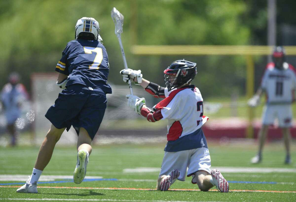 Weston's Greyson Collins (7) attempts to front as New Fairfield's Dylan Hanley (3) fires a shot from the knees in for a score in Saturday's Class M championship game.
