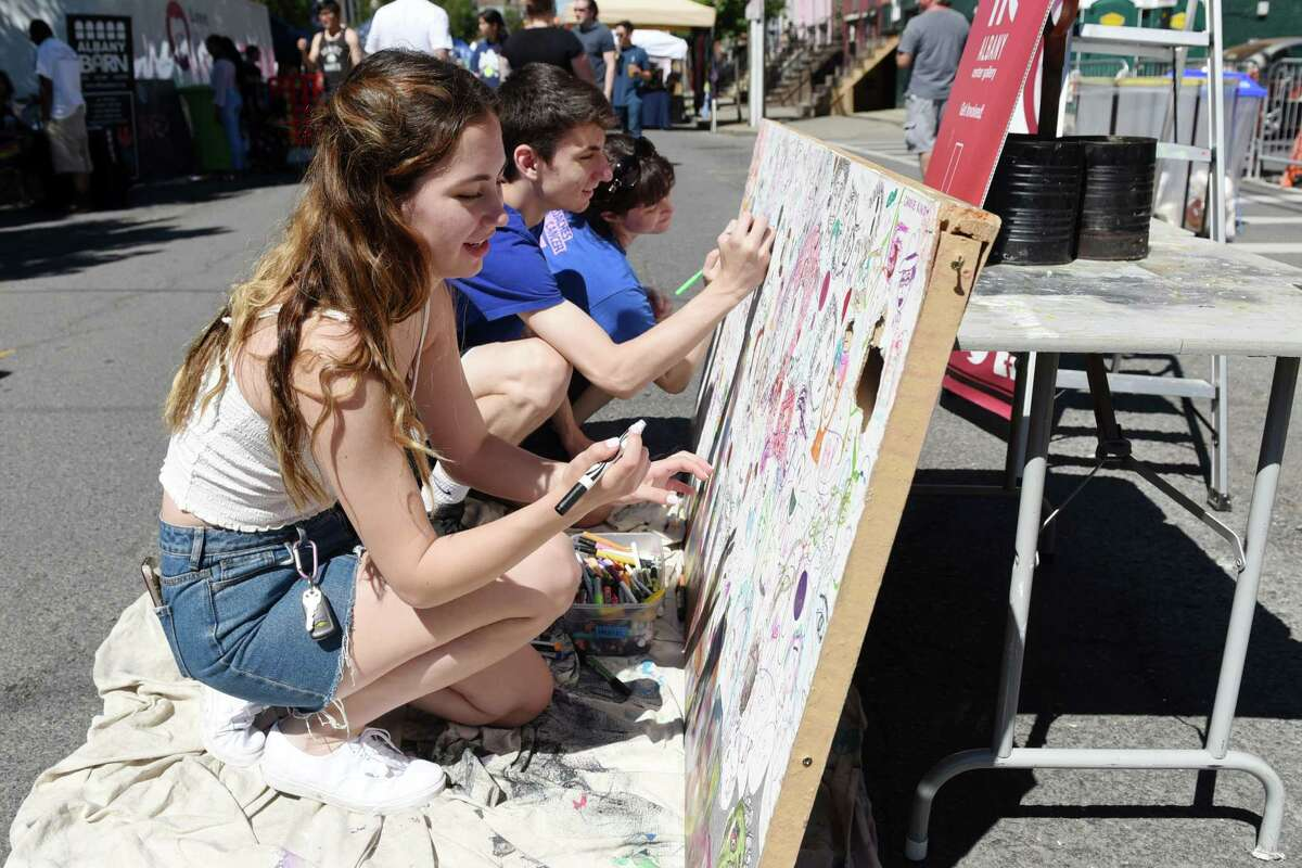 From left, Alyssa Decker, Cameron Decker and Jodi Skorupski draw faces on an Albany Center Gallery mural during Art on Lark in 2019. The event will be held this year on Saturday, Aug. 28. (Phoebe Sheehan/Times Union)