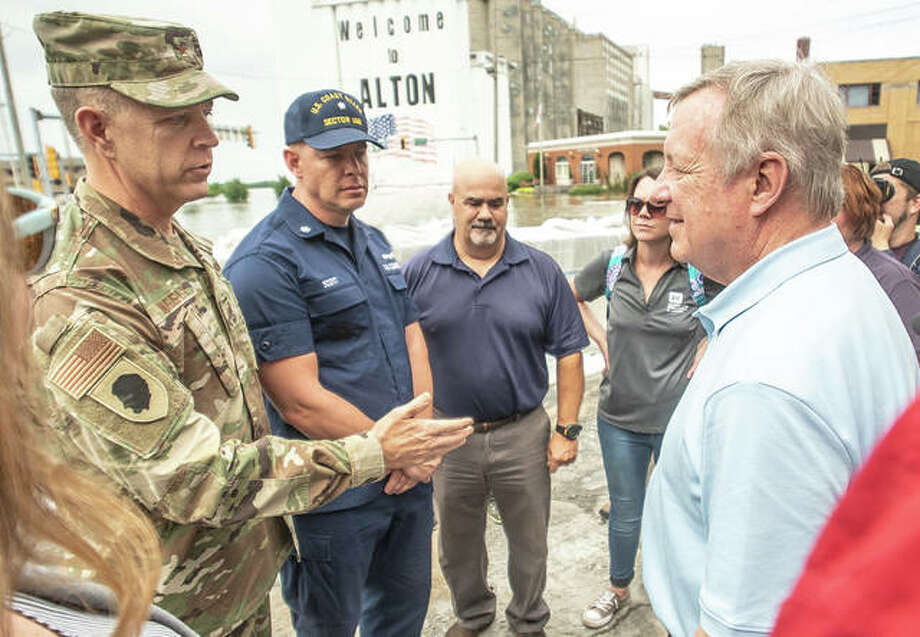 Brig. Gen. Richard Neely, the adjutant general of the Illinois National Guard, left, and Coast Guard Capt. Scott Stoermer, commander of the Upper Mississippi River sector, second from left, speak with U.S. Sen. Dick Durbin Saturday while surveying floodwaters in downtown Alton at the intersection of Broadway and Landmarks Boulevard. Photo: Nathan Woodside | The Telegraph