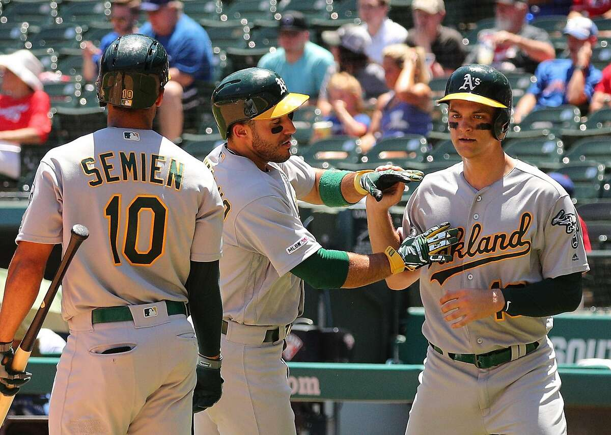 ARLINGTON, TEXAS - JUNE 08: Ramon Laureano #22 and Chad Pinder #18 of the Oakland Athletics celebrate after scoring on a double by Josh Phegley #19 of the Oakland Athletics in the fourth inning during game one of a doubleheader against the Texas Rangers at Globe Life Park in Arlington on June 08, 2019 in Arlington, Texas. (Photo by Richard Rodriguez/Getty Images)