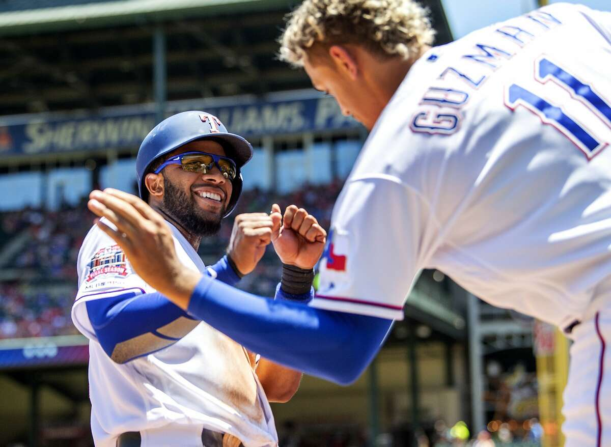 Texas Rangers' Elvis Andrus jokes around with Ronald Guzman (11) after scoring on a two-run home run by Nomar Mazara during the third inning of the first baseball game of a doubleheader against the Oakland Athletics, Saturday, June 8, 2019, in Arlington, Texas. (AP Photo/Jeffrey McWhorter)
