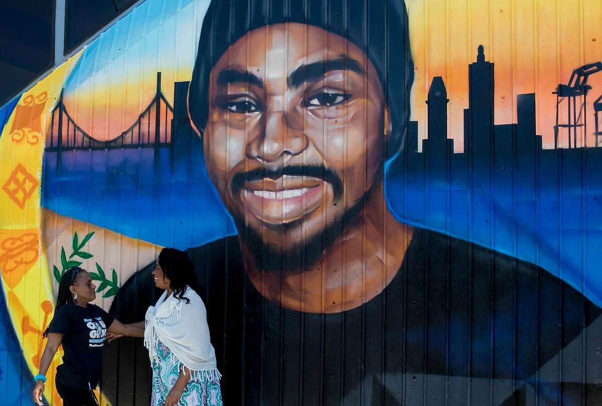Wanda Johnson (right), mother of the late Oscar Grant, greets a friend while standing underneath a large mural honoring her son during a mural and street naming unveiling for Oscar Grant at Fruitvale BART Station in Oakland, Calif. Saturday, June 8, 2019.