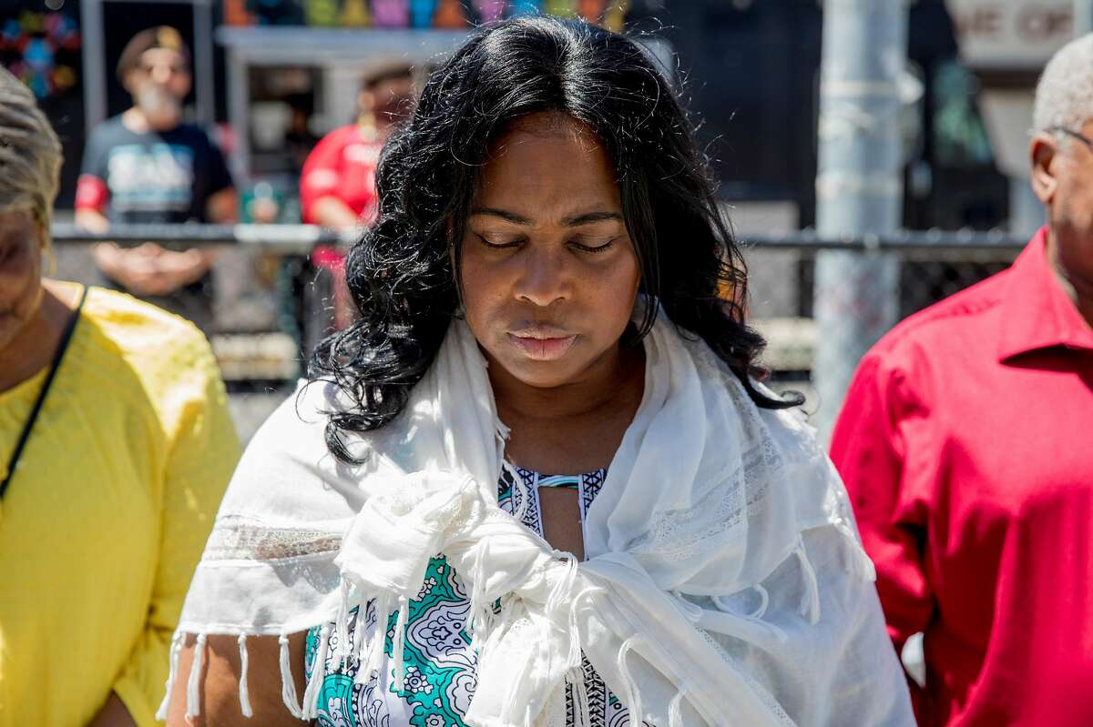 Wanda Johnson, mother of the late Oscar Grant, bows her head in prayer during a mural and street naming unveiling for Oscar Grant at Fruitvale BART Station in Oakland, Calif. Saturday, June 8, 2019.