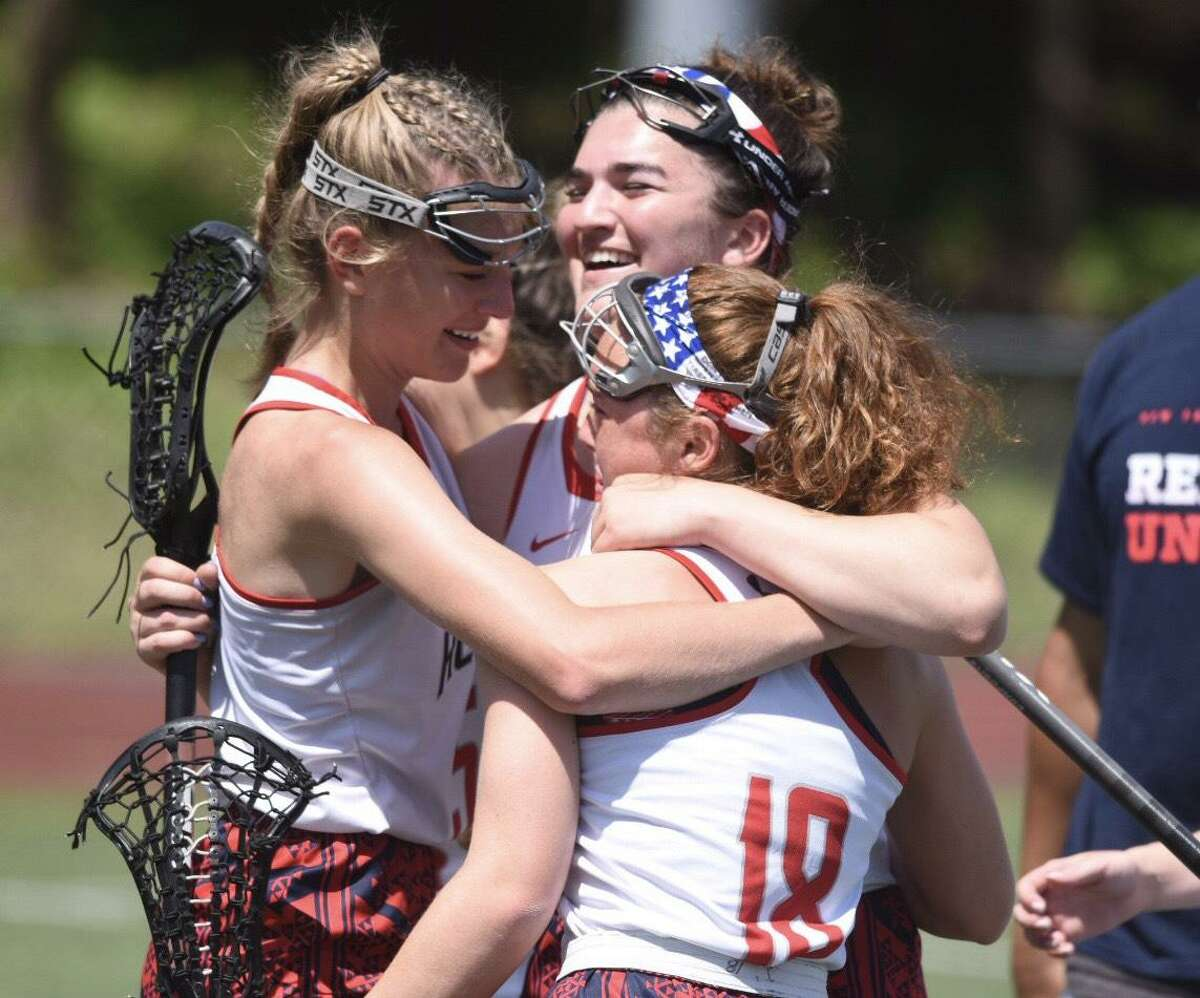 New Fairfield's Katelyn Nieves (back), Eileen Rattigan (left) and Maria Zegarelli (18) celebrate after the Rebels defeated Stonington in the CIAC Class S girls lacrosse final at Jonathan Law High School in Milford on Saturday, June 8, 2019.