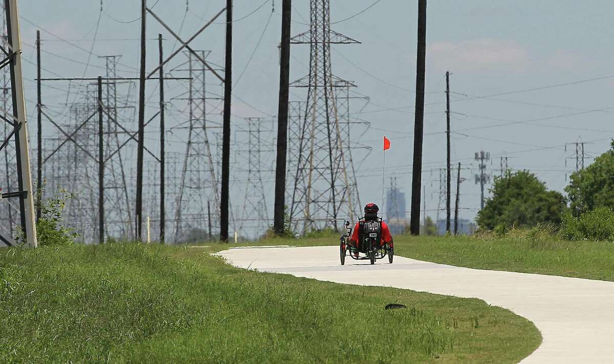 Carl Pointer rides his recumbent bicycle on the new recreational trail along a CenterPoint Energy easement near Hiram Clarke Road and Sims Bayou on June 8.