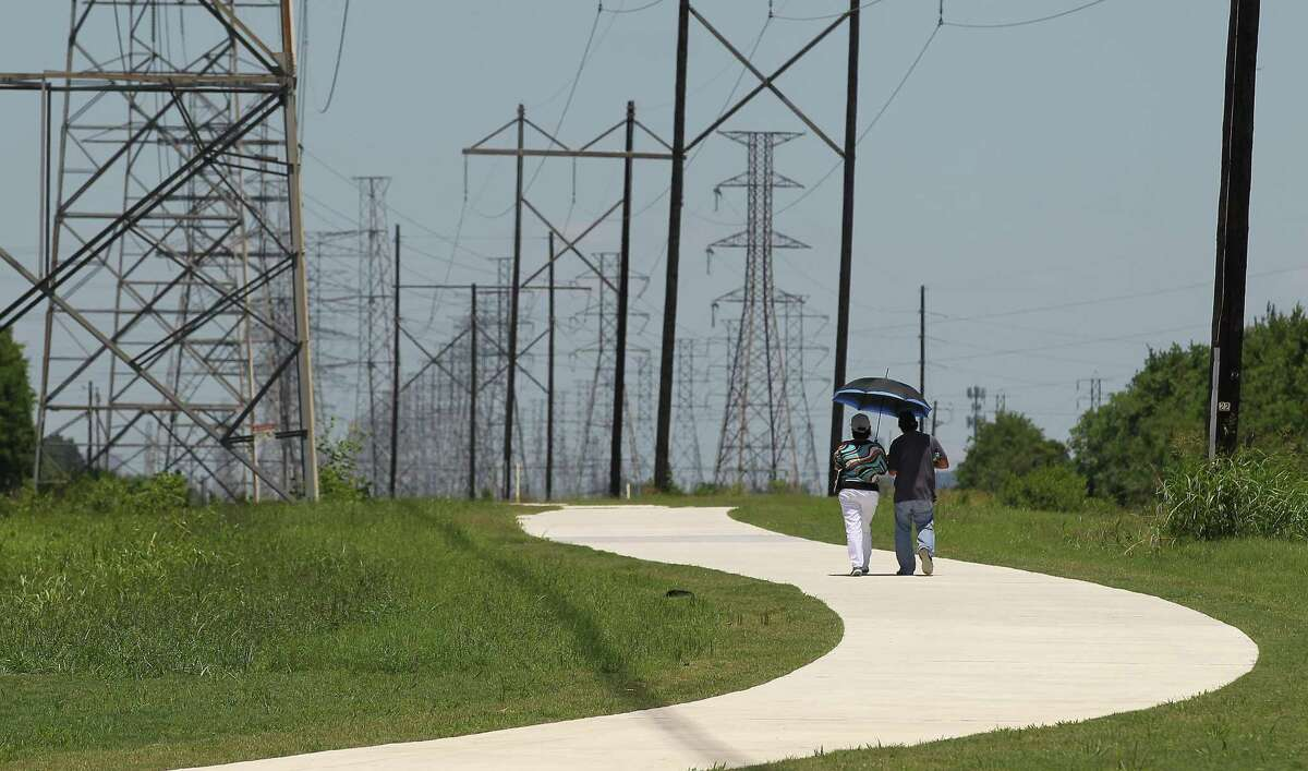 A couple enjoy a stroll on the new recreational trail along a CenterPoint Energy easement near Hiram Clarke Road and Sims Bayou on June 8.