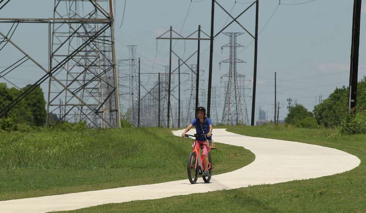 Janice Kruse rides on the new recreational trail along a CenterPoint Energy easement near Hiram Clarke Road and Sims Bayou on June 8.