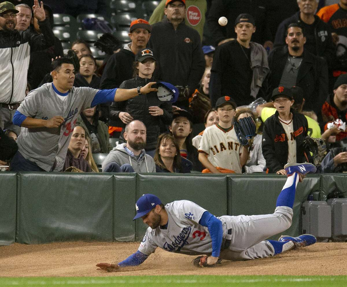 Los Angeles Dodgers left fielder Chris Taylor trips over the bullpen pitcher's mound while chasing a foul ball by San Francisco Giants' Brandon Belt during the sixth inning of a baseball game, Friday, June 7, 2019, in San Francisco. Belt eventually walked and scored. (AP Photo/D. Ross Cameron)