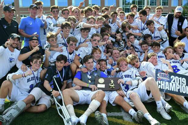 The Darien Blue Wave celebrates after winning against the Wilton Warriors in the Class L boys lacrosse championship on Saturday in Norwalk.