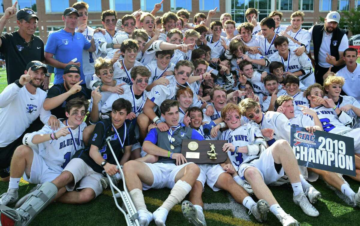 The Darien High School Blue Wave celebrates after winning against the Wilton High School Warriors in their Class L boys lacrosse championship Saturday, June 8, 2019, at Brien McMahon High School in Norwalk, Conn.