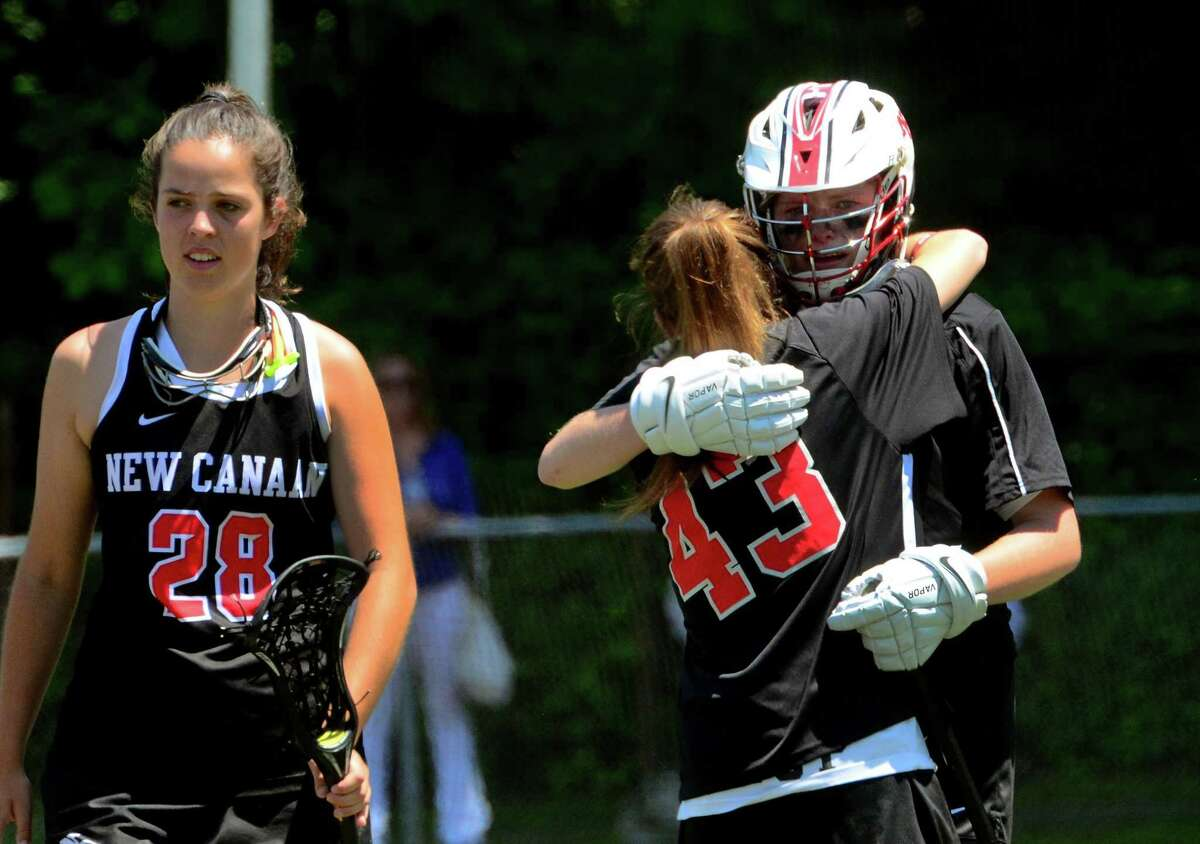New Canaan goalie Caroline O'Dea is comforted by teammate Shea Hobbs (43) after the team lost to Darien in girls Class L lacrosse action in Milford, Conn., on Saturday June 8, 2019.