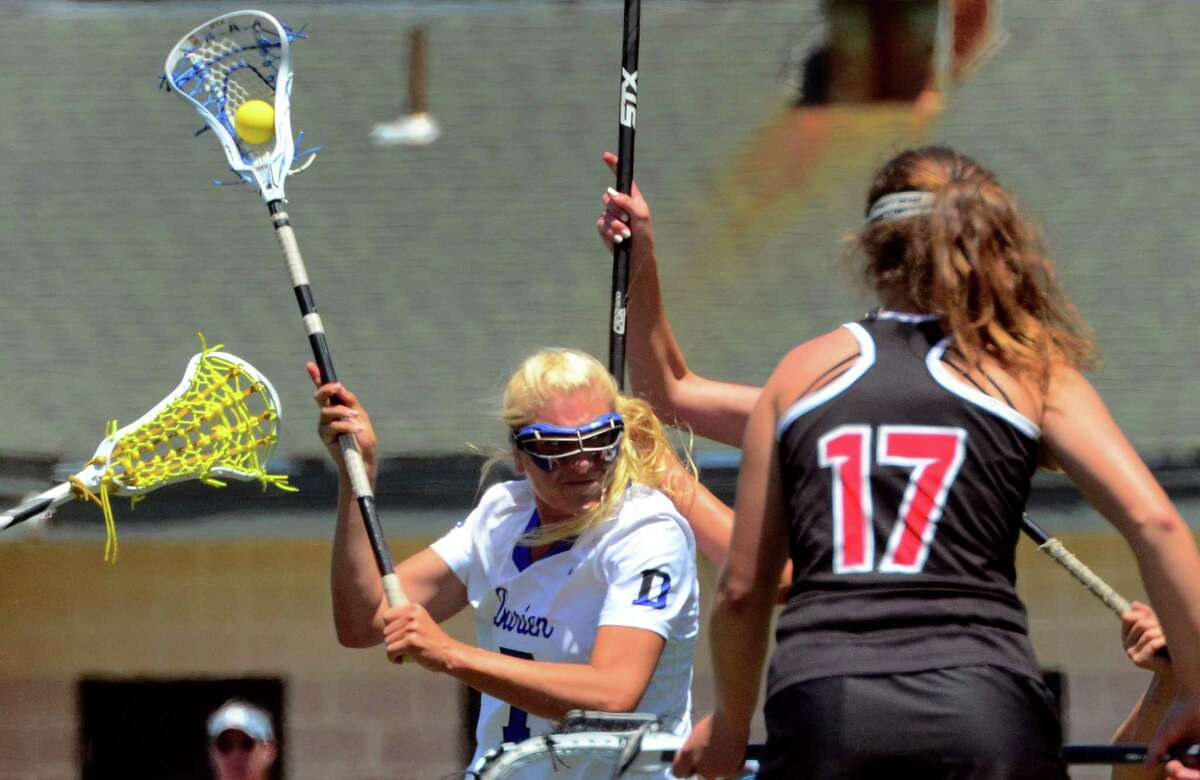 Darien's Charlotte Wittstock (7) attempts a goal shot during the Class L championship against New Canaan on Saturday.