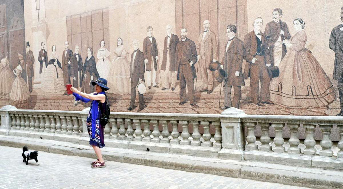 A tourist takes a photo in front of a painting made from sand in Havana, Cuba on Saturday, June 8, 2019 in Havana.