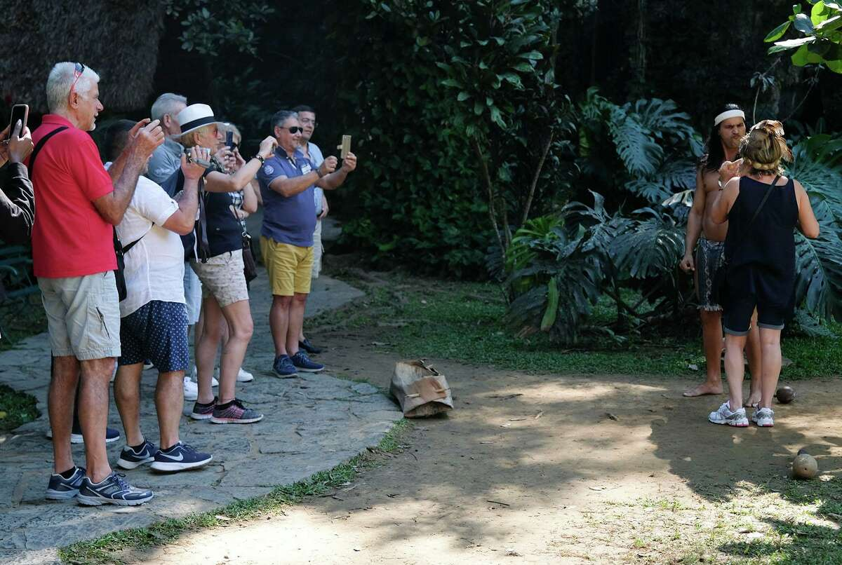 Tourists take photos during a presentation outside caves in the valley of Mogotes in Cuba on January 14, 2019.