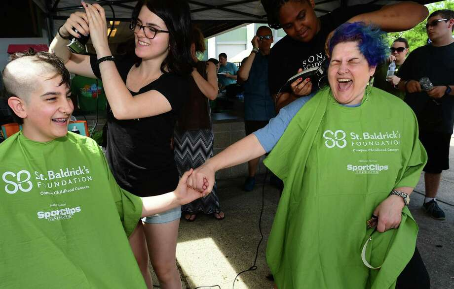 Math teacher Sue Weber, right, and her son, Jackson Weber, 13, have their heads shaved as Norwalk High School hosts its annual St. Baldrick's Foundation head-shaving event Saturday in Norwalk. The event raises funds and awareness for lifesaving childhood cancer research with a goal to raise $10,000. Photo: Erik Trautmann / Hearst Connecticut Media / Norwalk Hour
