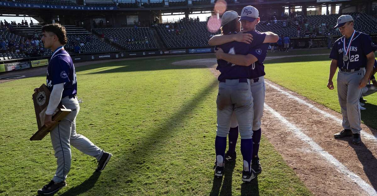 Fort Bend Ridge Point Gabe Colaianni, (14), carries the team's runner-up trophy to the dugout as Hayde Key, (4), gets a hug from Mitch Cashion, (30), and Dylan Bobo, (22), walks off the field after losing to Southlake Carrol in the UIL Class 6A state championship held at the Dell Diamond, Thursday, Dec. 31, 2015, in Round Rock, Texas. Fort Bend Ridge Point lost to Southlake Carroll 17-0. (Rodolfo Gonzalez for Houston Chronicle)