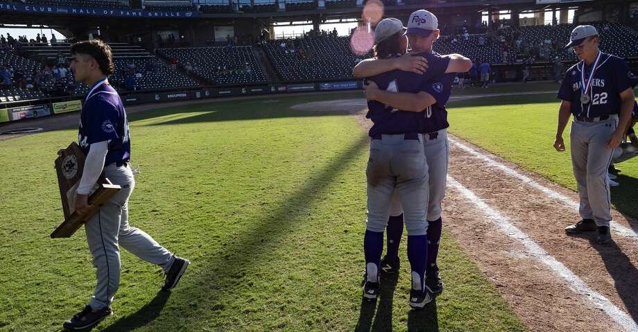 Fort Bend Ridge Point Gabe Colaianni, (14), carries the team's runner-up trophy to the dugout as Hayde Key, (4), gets a hug from Mitch Cashion, (30), and Dylan Bobo, (22), walks off the field after losing to Southlake Carrol in the UIL Class 6A state championship held at the Dell Diamond, Thursday, Dec. 31, 2015, in Round Rock, Texas. Fort Bend Ridge Point lost to Southlake Carroll 17-0.   (Rodolfo Gonzalez for Houston Chronicle) Photo: Rodolfo Gonzalez/Houston Chronicle