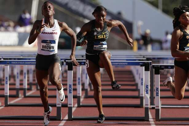 Arkansas' Janeek Brown, left, edges out LSU's Tonea Marshall, center, and Southern California's Chanel Brissett, right, to win the women's 100 hurdles during the NCAA outdoor track and field championships in Austin, Texas, Saturday, June 8, 2019. (AP Photo/Eric Gay)
