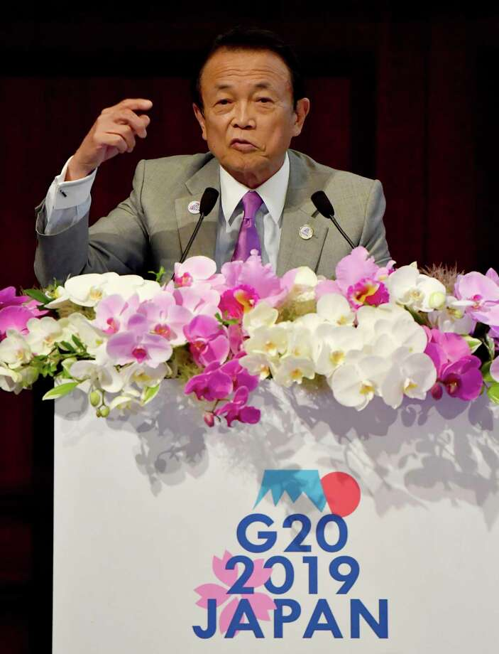 Japanese Finance Minister Taro Aso delivers opening remarks during the G20 Ministerial Symposium on International Taxation in the G20 Finance Ministers and Central Bank Governors meeting in Fukuoka, southern Japan Saturday, June 8, 2019. Finance chiefs of the Group of 20 major economies meeting in the Japanese city of Fukuoka are debating how to revise tax systems to ensure big companies pay their fair share and support economies as global growth slows. (Toshifumi Kitamura/Pool Photo via AP) Photo: Toshifumi Kitamura / Pool AFP