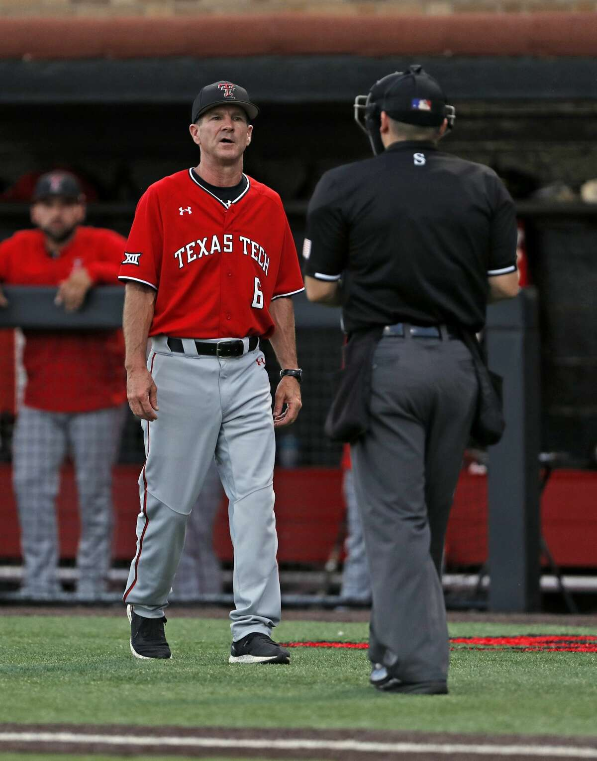 Texas Tech coach Tim Tadlock talks to umpire Ryan Morehead during the ninth inning in Game 2 of the team's NCAA college baseball tournament super regional against Oklahoma State, Saturday, June 8, 2019, in Lubbock, Texas. (AP Photo/Brad Tollefson)