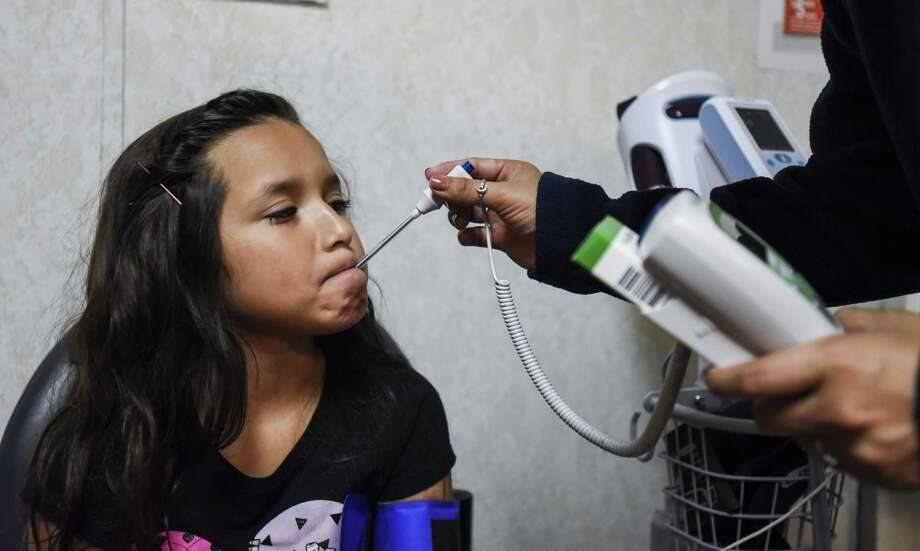 Tania Torres, a nurse with the Gulf Coast Health Center, checks Elena Solis, 7, body temperature in the clinic Tuesday afternoon in Port Arthur. Photo taken on Tuesday, 06/04/19. Ryan Welch/The Enterprise Photo: Ryan Welch, Beuamont Enterprise / The Enterprise / © 2019 Beaumont Enterprise